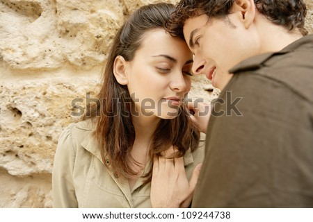 Attractive young couple having a romantic moment and leaning on a texture wall while on holidays. - stock photo