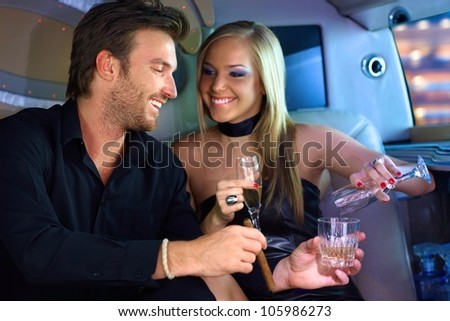Attractive young couple having fun in limousine, drinking.