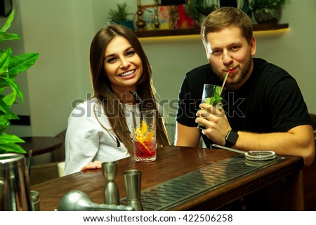 Attractive young couple having fun with cocktails at the bar table - stock photo