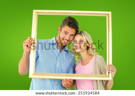 Attractive young couple holding picture frame against green vignette - stock photo