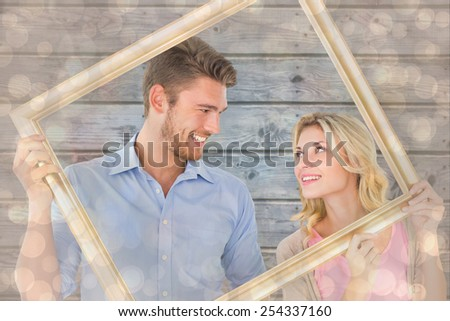 Attractive young couple holding picture frame against light glowing dots design pattern - stock photo
