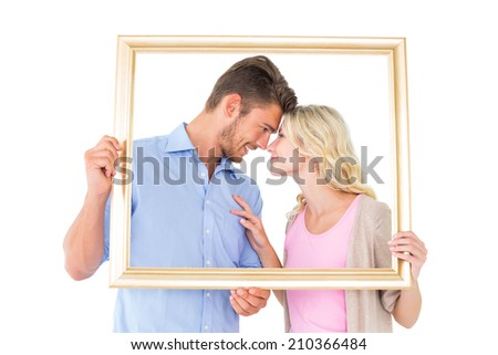 Attractive young couple holding picture frame on white background - stock photo