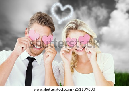 Attractive young couple holding pink hearts over eyes against green grass under grey sky - stock photo