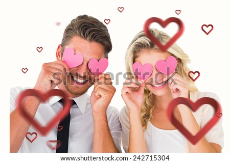 Attractive young couple holding pink hearts over eyes against hearts - stock photo