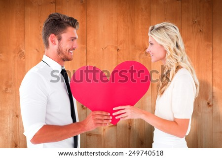 Attractive young couple holding red heart against wooden planks - stock photo