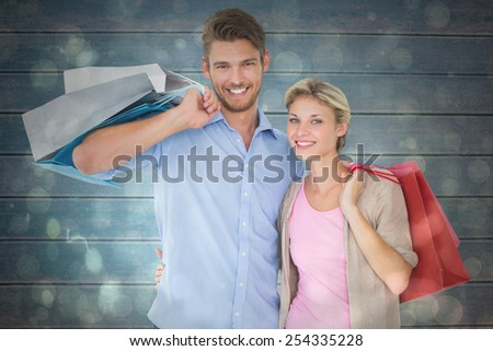 Attractive young couple holding shopping bags against black abstract light spot design - stock photo