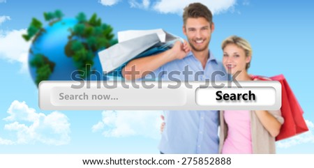 Attractive young couple holding shopping bags against blue sky - stock photo
