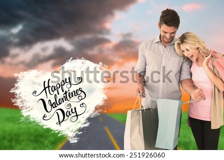 Attractive young couple holding shopping bags against cloud heart - stock photo