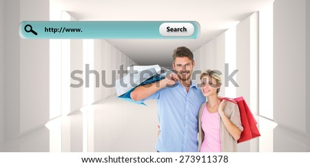 Attractive young couple holding shopping bags against digitally generated room - stock photo