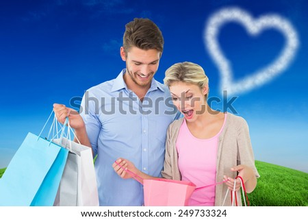 Attractive young couple holding shopping bags against green hill under blue sky - stock photo