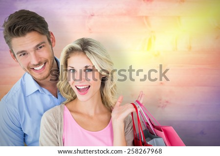 Attractive young couple holding shopping bags against yellow and purple planks - stock photo