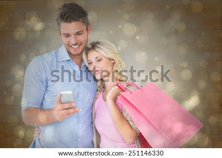 Attractive young couple holding shopping bags looking at smartphone against black abstract light spot design - stock photo