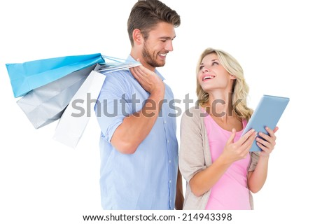 Attractive young couple holding shopping bags looking at tablet pc on white background - stock photo