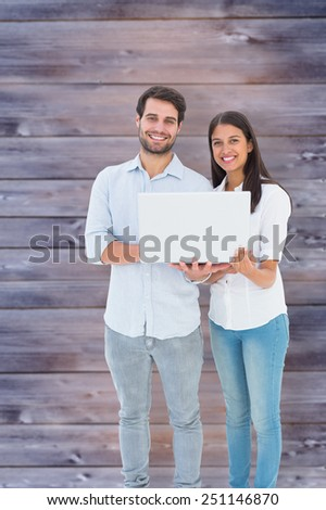 Attractive young couple holding their laptop against faded grey wooden planks - stock photo