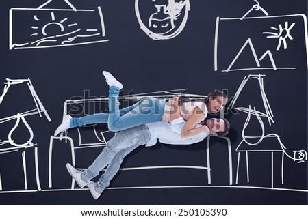 Attractive young couple hugging each other against blackboard - stock photo