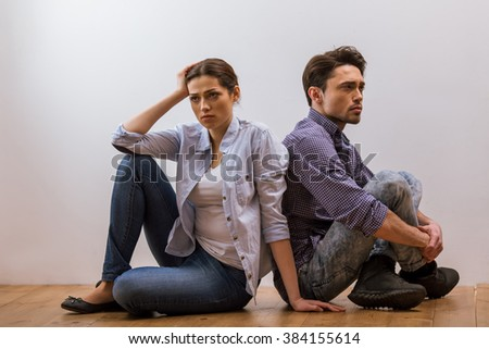 Attractive young couple in casual clothes sitting back to back on wooden floor against white background after quarreling - stock photo