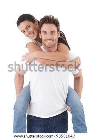 Attractive young couple in love, man carrying woman pickaback, smiling happily.?
