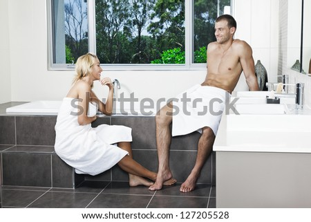 Attractive young couple in stylish twin bathroom - stock photo