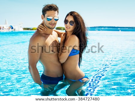 Attractive young couple in swimming pool wearing sunglasses and hugging at each other  - stock photo