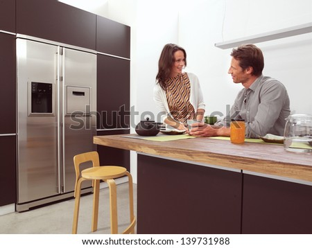 Attractive young couple in the kitchen - stock photo