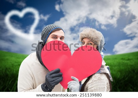 Attractive young couple in warm clothes holding red heart against green field under blue sky - stock photo