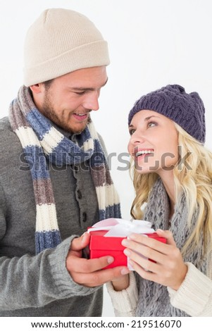 Attractive young couple in warm clothing holding gift over white background - stock photo