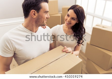 Attractive young couple is moving, looking at each other and smiling while standing among cardboard boxes. Man is holding a box - stock photo
