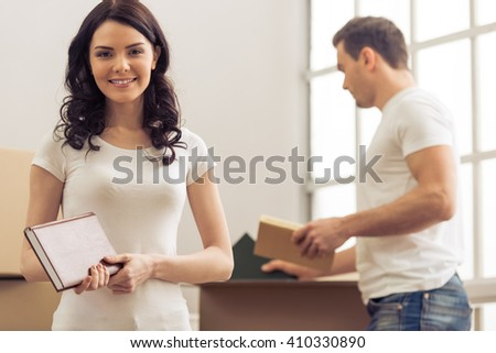 Attractive young couple is moving, packing things in cardboard boxes. Woman is looking at camera and smiling - stock photo