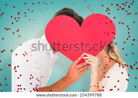 Attractive young couple kissing behind large heart against blue vignette background - stock photo