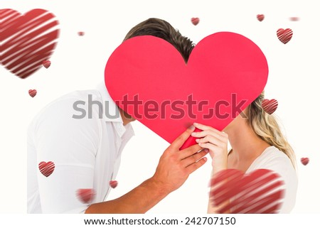 Attractive young couple kissing behind large heart against hearts - stock photo