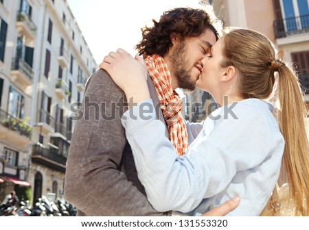 Attractive young couple kissing in a classic architecture city during their vacation in a sunny destination city. - stock photo