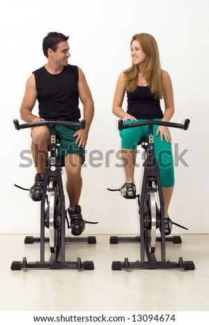 Attractive young couple looking at each other and smiling while working out on exercise bikes. Vertically framed, isolated shot. - stock photo