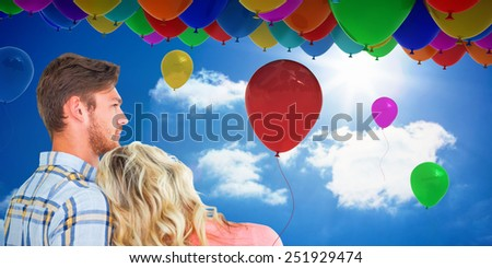 Attractive young couple looking together against bright blue sky with clouds - stock photo