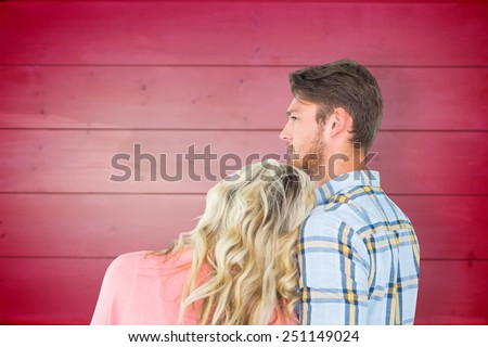 Attractive young couple looking together against wooden planks background - stock photo