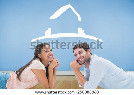 Attractive young couple looking up against blue room with wooden floor - stock photo
