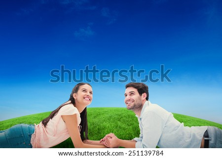 Attractive young couple looking up against green hill under blue sky - stock photo