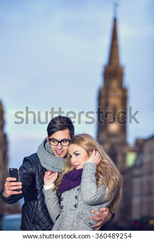 Attractive young couple making selfie on Royal Mile in Edinburgh city, Scotland  - stock photo
