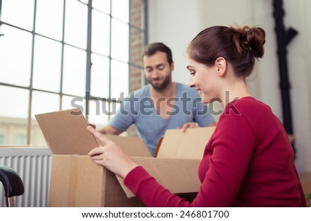 Attractive young couple moving house getting ready to unpack a cardboard carton of personal possessions below a big window - stock photo
