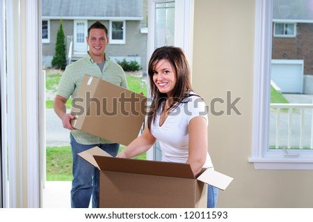 Attractive Young Couple Moving Into A New House - stock photo