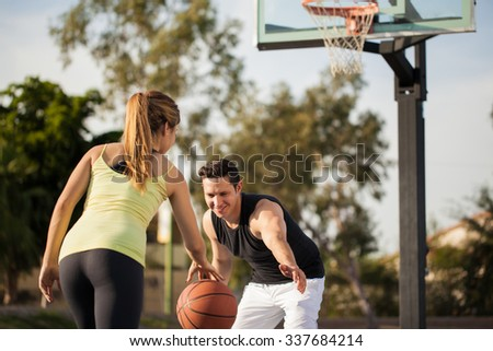 Attractive young couple playing basketball against each other outdoors - stock photo