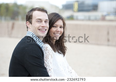 Attractive young couple posing near the beach.