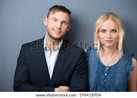 Attractive young couple posing side by side facing the camera with a smile standing against a grey studio background - stock photo