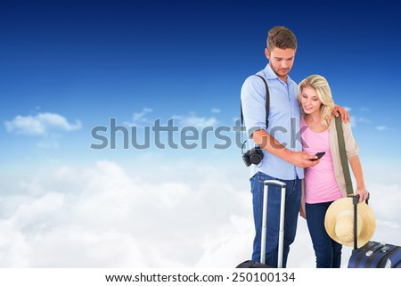 Attractive young couple ready to go on vacation against bright blue sky over clouds - stock photo