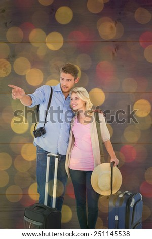 Attractive young couple ready to go on vacation against close up of christmas lights - stock photo