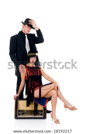Attractive young couple, retro look with old radio.    Studio shot, white background. - stock photo