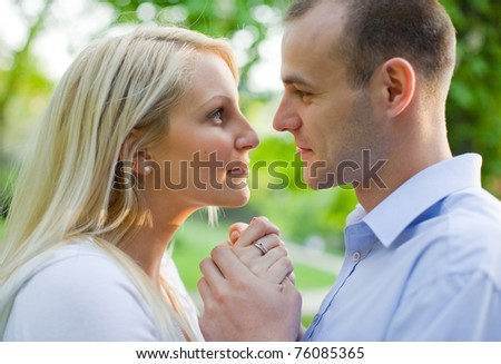 Attractive young couple romancing in the park at sunset. - stock photo
