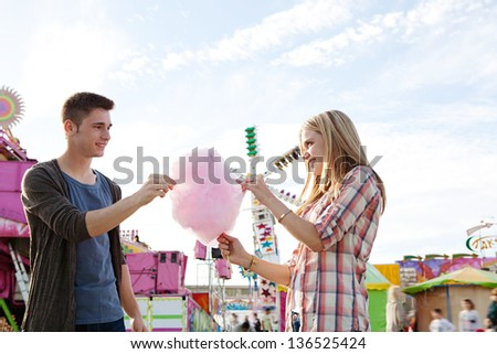 Attractive young couple sharing a pink cotton candy floss sweet wile enjoying a funfair ground wit colorful rides and a blue sky, smiling. - stock photo