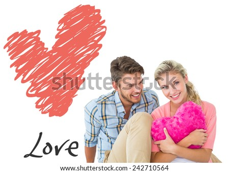 Attractive young couple sitting holding heart cushion against love heart - stock photo