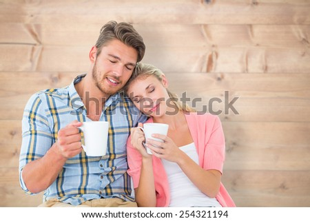 Attractive young couple sitting holding mugs against bleached wooden planks background - stock photo