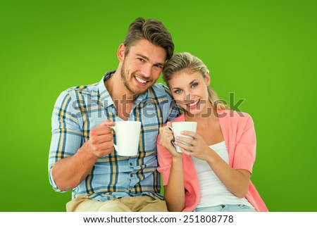 Attractive young couple sitting holding mugs against green vignette - stock photo